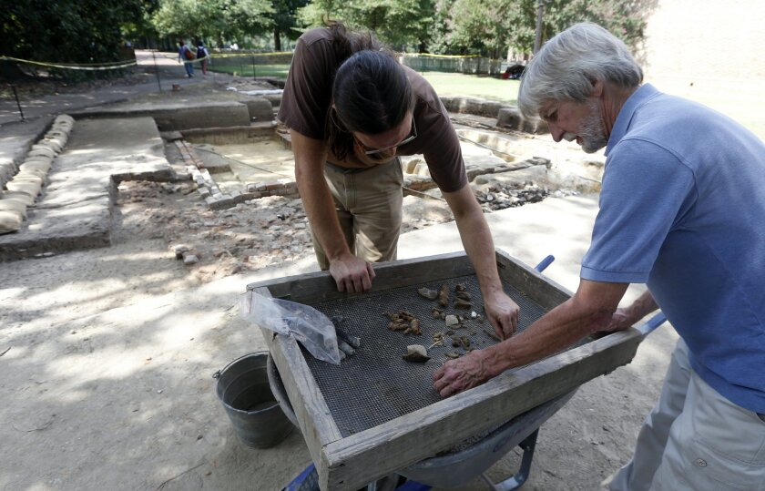 ADVANCE FOR MONDAY, SEPT. 1, AND THEREAFTER - In this photo taken on Thursday, Aug. 28, 2014, Colonial Williamsburg archaeologist Andrew Edwards, right, and John Elliott Jones, left, sort through artifacts from a dig next to the Wren Building on the campus of William & Mary in Williamsburg, Va. Archaeologists, who believe they may have found the remnants of a centuries old brewhouse, wrapped up the intensive excavation work on the site on Friday, and will now turn to laboratories to analyze everything they've found. (AP Photo/Steve Helber)