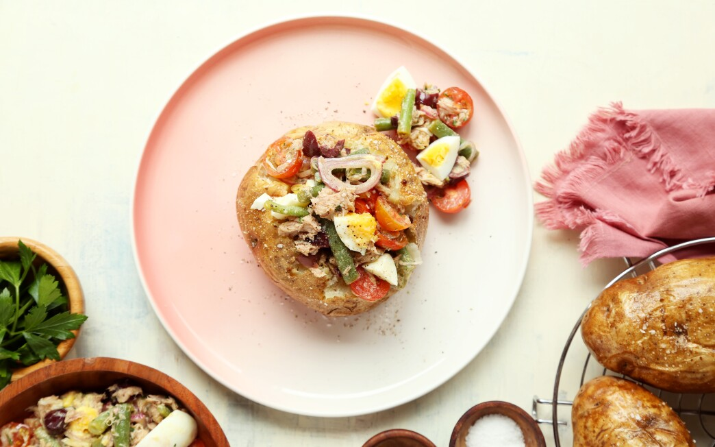 Niçoise salad's traditional fingerling spuds transform into large baked potatoes topped with the classic salad's veggies.
