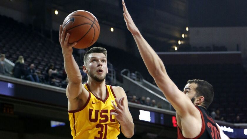 Southern California's Nick Rakocevic, left, goes to basket while defended by Stanford's Josh Sharma,