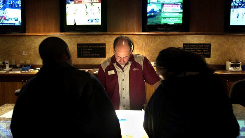 A Mandalay Bay employee takes a bet at the sports book in Las Vegas, where millions of dollars are gambled each week in the fall on college football.