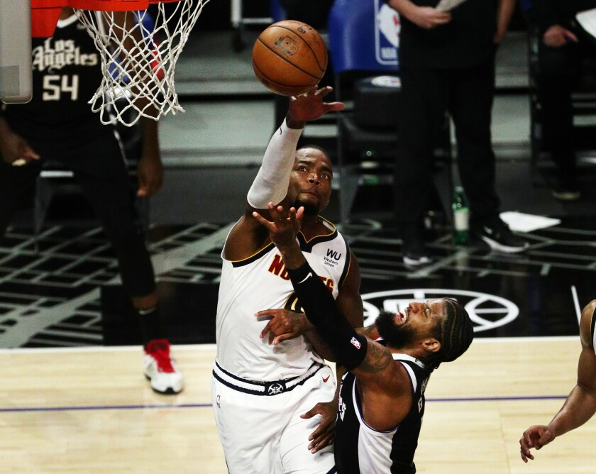 LA Clippers guard Paul George drives to the basket and gets his shot just over Denver Nuggets forward Paul Millsap.