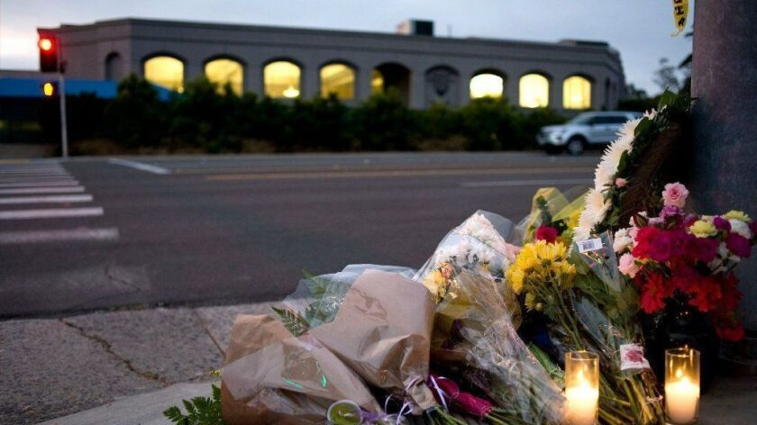 Flowers and candles sit at a makeshift shrine across the street from Chabad of Poway in San Diego County.