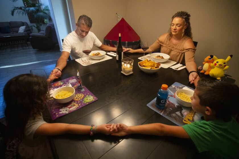 Jon and Roxanne Hatami with 4-year-old Lindsey Beth and Jon Jr., 7, before dinner in their Santa Clarita Valley home.