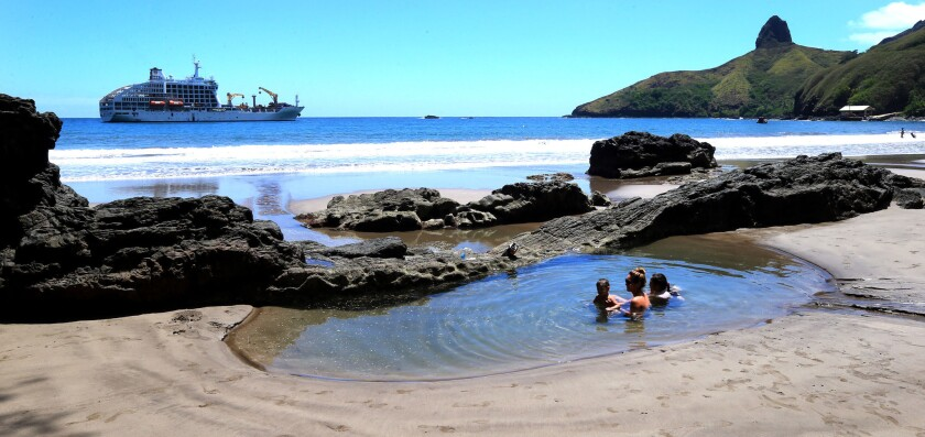 A local Hiva Oa Island family plays in a natural ocean pool as the Aranui 5 ship anchors, background. Hiva Oa is part of the Marquesas chain of Islands.
