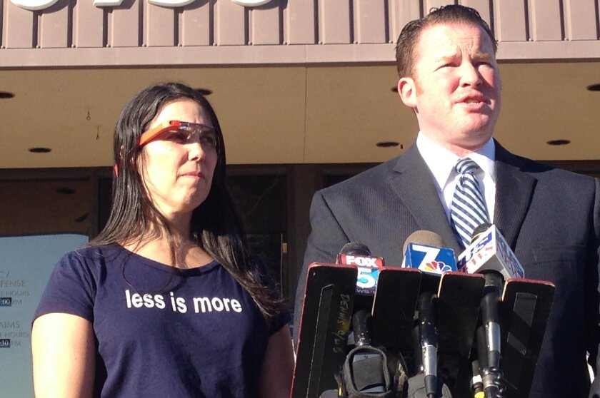 Charges against a motorist who was ticketed for wearing Google Glass while driving were dismissed in San Diego County traffic court on Thursday. Cecelia Abadie, left, wears the high-tech glasses while her attorney, William Concidine, talks to the media.