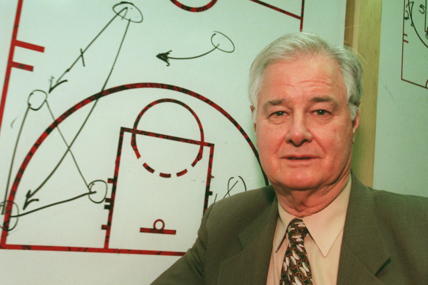 """Chicago Bulls' assistant coach Tex Winter stands in front of a diagram of his """"triangle"""" offense in 1997."""