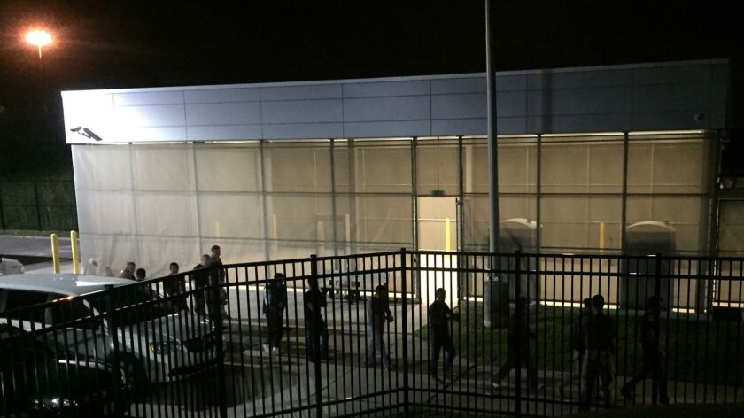 In this image provided by Jodie Bowers, detainees are escorted into an Immigration and Customs Enfor