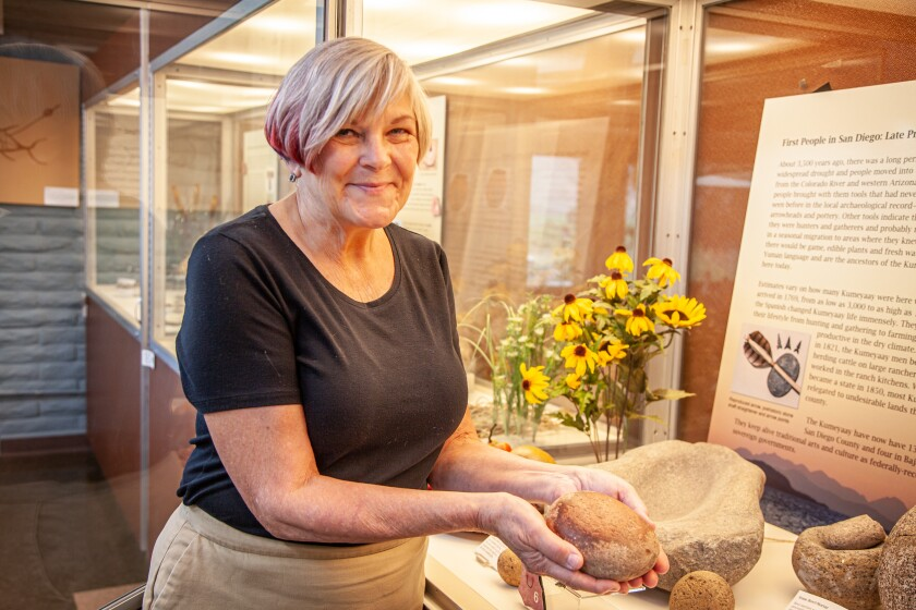 Cindy Stankowski, executive director of the San Diego Archaeological Center, holds a grinding stone from a local Native American archaeological site.