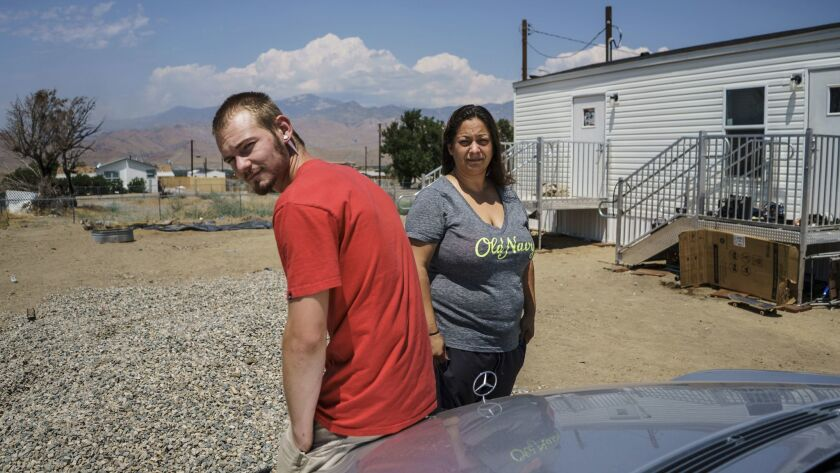 Melanie Perea and her boyfriend, Erik Kirby, outside their makeshift FEMA-provided trailer home in L