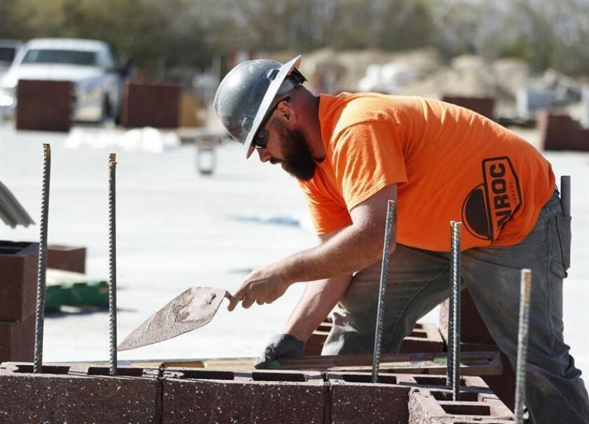 Vista de un trabajador de construcción pone cemento en unos ladrillos. EFE/Archivo
