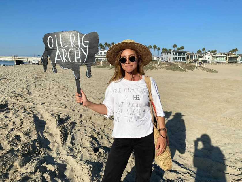 A woman standing on a beach holds a sign