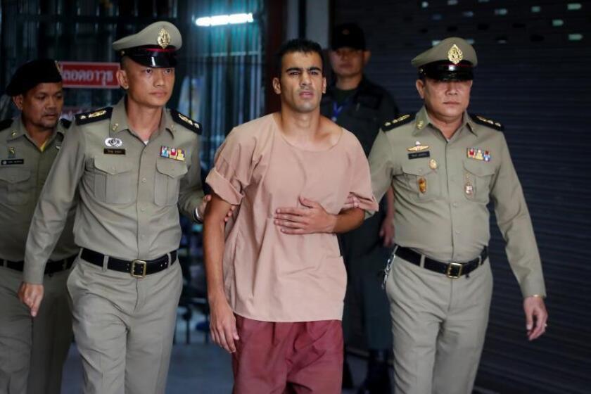 El futbolista y refugiado bareiní Hakeem Al Araibi (c) es escoltado por dos funcionarios de prisiones tailandeses tras asistir a una vista de su proceso de extradición ante el Tribunal Criminal este lunes en Bangkok (Tailandia). EFE