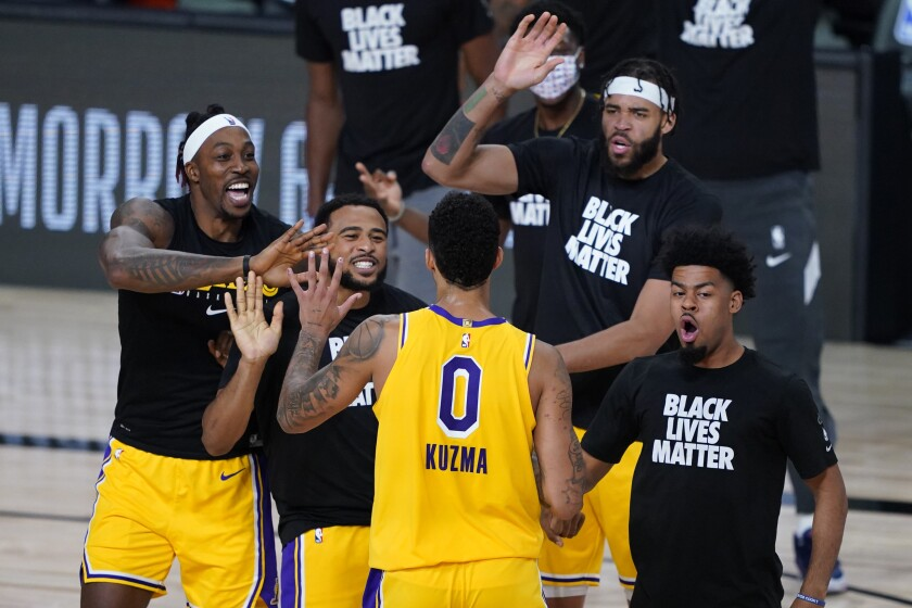 Los Angeles Lakers' Kyle Kuzma (0) is congratulated by teammates after hitting a game-winning 3-pointer against the Denver Nuggets during the second half of an NBA basketball game Monday, Aug. 10, 2020, in Lake Buena Vista, Fla. The Lakers won 124-121. (AP Photo/Ashley Landis, Pool)