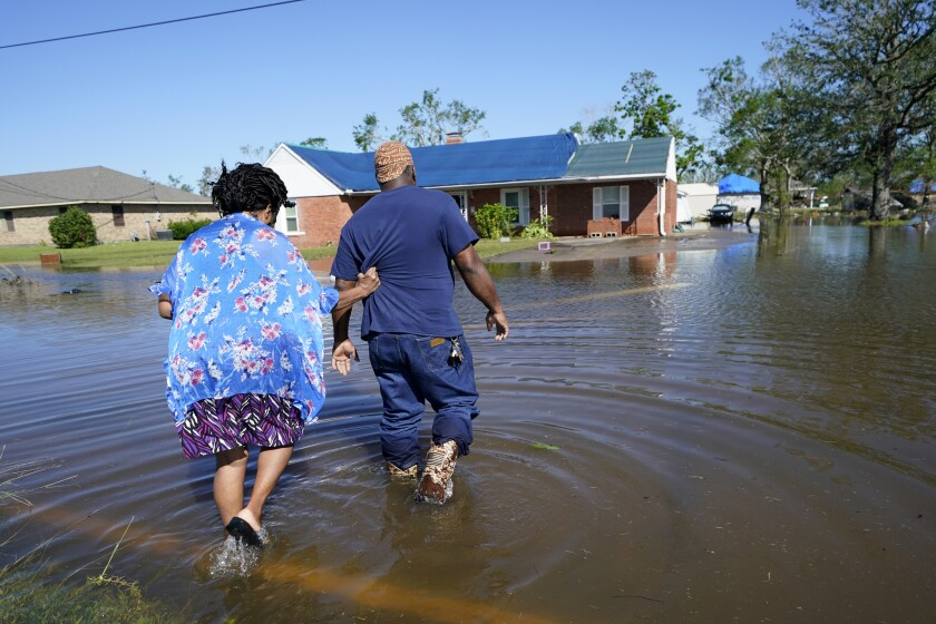 Soncia King holds onto her husband Patrick King in Lake Charles, La., Saturday, Oct. 10, 2020, as they walk through the flooded street to their home, after Hurricane Delta moved through on Friday. (AP Photo/Gerald Herbert)