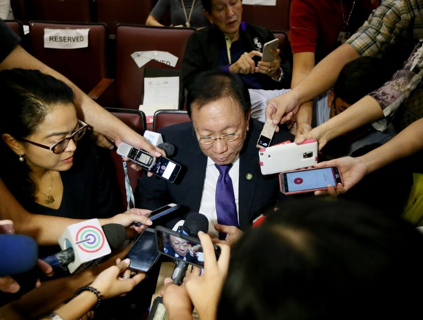 New Philippine Solicitor General Jose Calida talks to the media during a break in the forum on Tuesday's ruling by the Hague-based UN international arbitration tribunal favoring the Philippines in its case against China on the dispute in South China Sea Friday, July 15, 2016 in suburban Quezon city