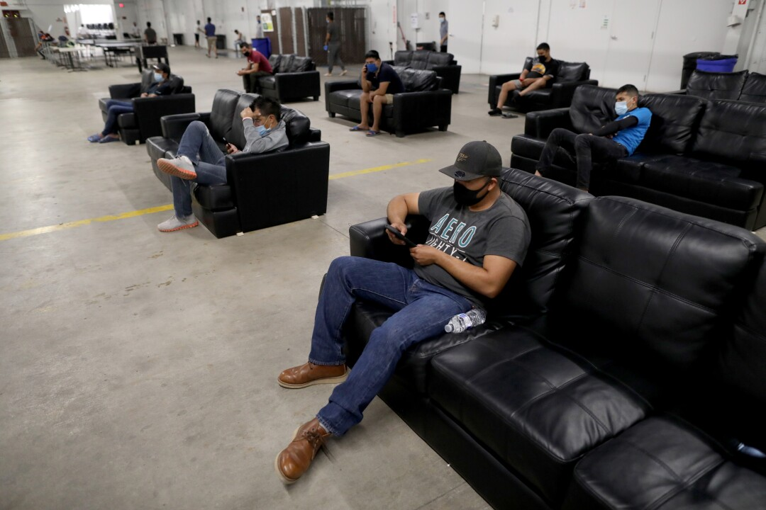 After finishing work, farmworkers relax in the living space practicing social distancing