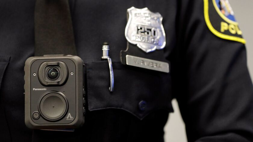 A police officer displays how a body cam is worn during a news conference in Newark, N.J. on April 26.