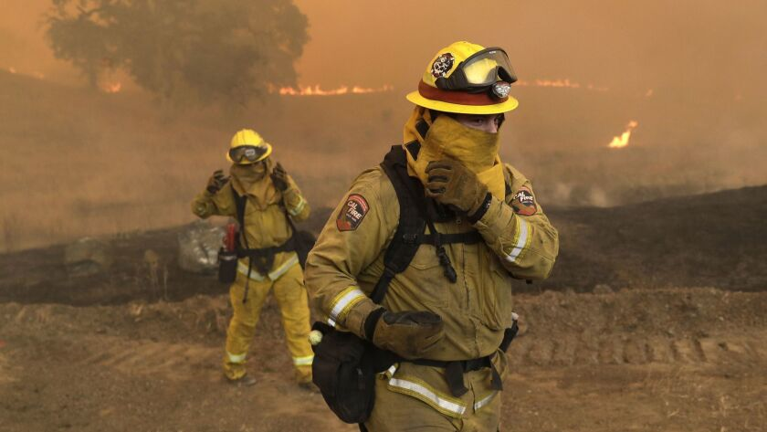 Firefighters with Cal Fire Mendocino Unit cover themselves from smoke and ash created by an advancing wildfire Monday, in Lakeport, Calif. A pair of wildfires that prompted evacuation orders for thousands of people are barreling toward small lake towns in Northern California.