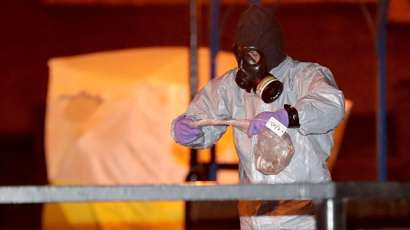 Police officers in protective suits and masks work on Tuesday at the scene of the poisoning of Sergei Skripal in Salisbury, England.
