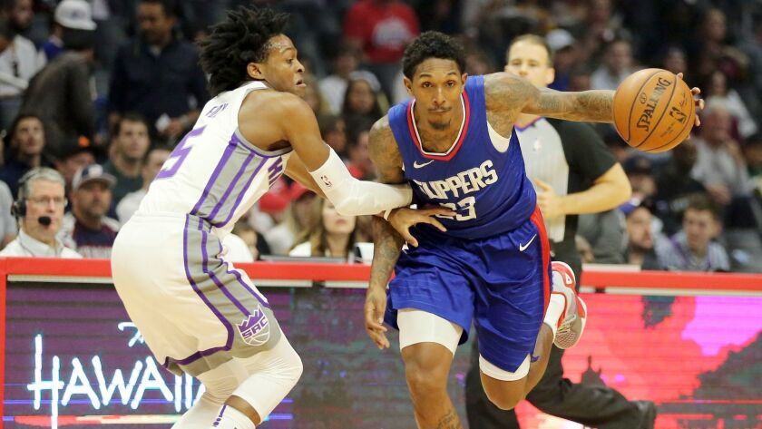 Sacramento Kings guard De'Aaron Fox defends as Clippers guard Lou Williams drives in the first quarter.