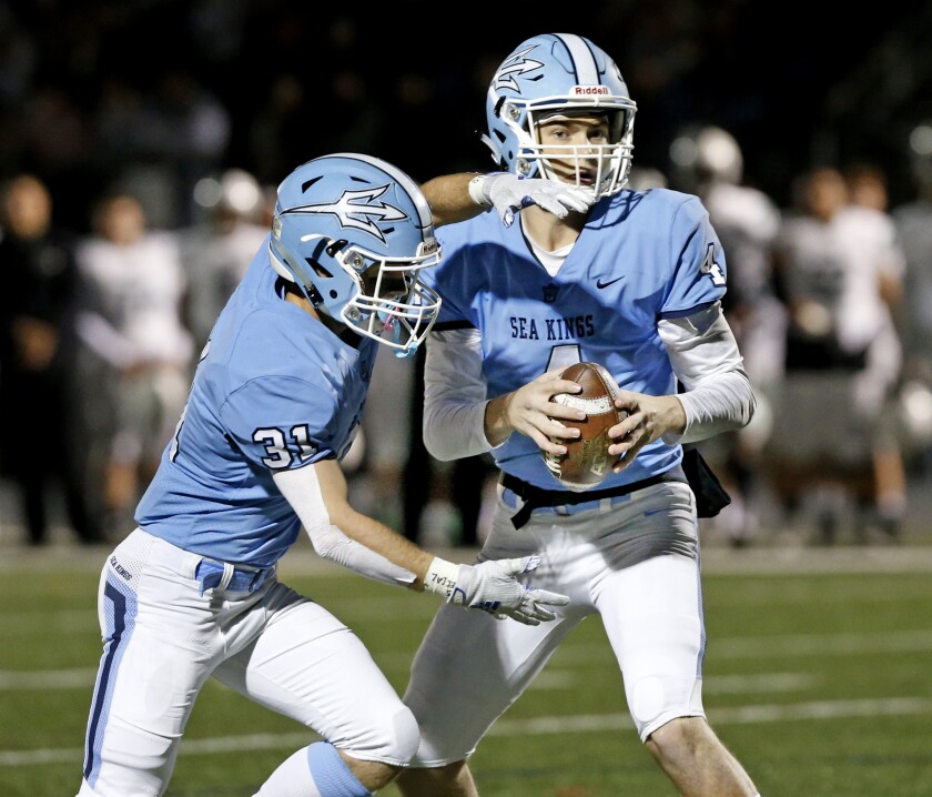 Corona del Mar quarterback Ethan Garbers, right, and running back Riley Binnquist execute a play Saturday night.