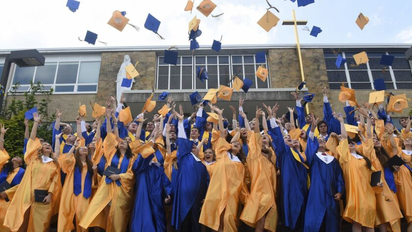 Marian Catholic High School graduates toss their caps into the air after posing for a group photo af