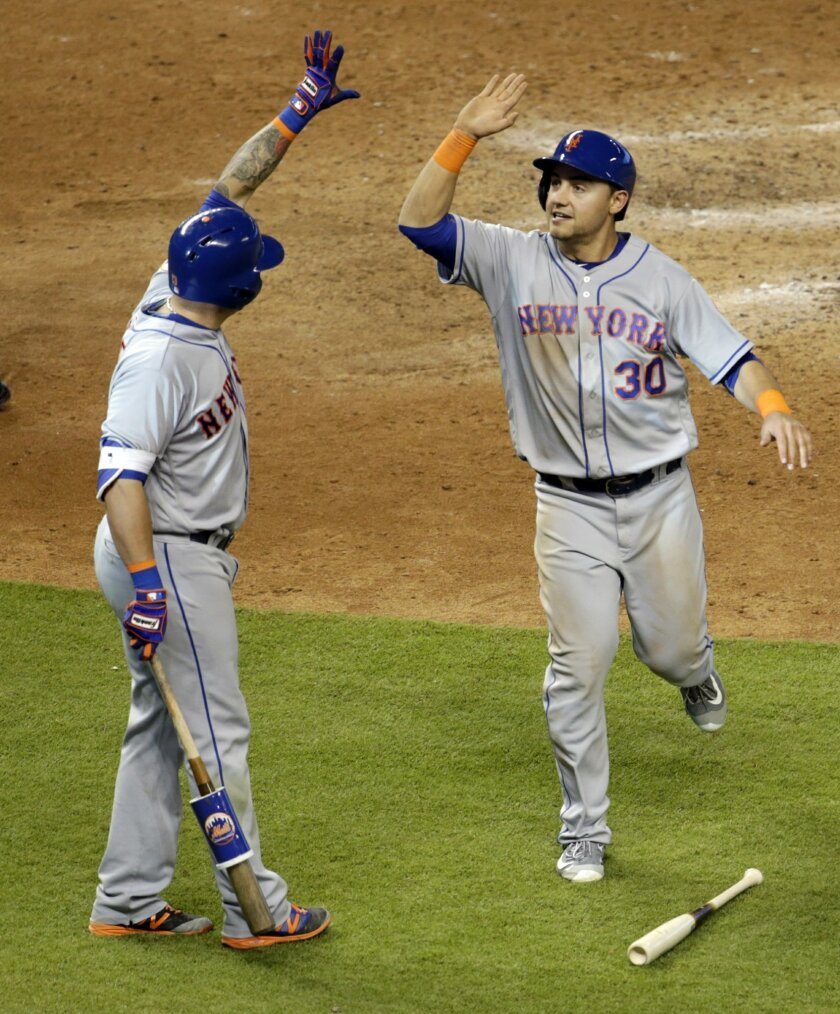 New York Mets' Michael Conforto (30) is greeted by Asdrubal Cabrera, left, after scoring on a single hit by Matt Reynolds in the eighth inning of a baseball game against the Miami Marlins, Saturday, June 4, 2016, in Miami. (AP Photo/Lynne Sladky)