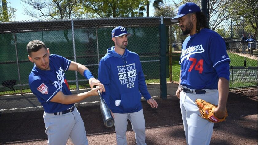 Dodgers hitting coach Robert Van Scoyoc, center, speaks with catcher Austin Barnes, left, and closer Kenley Jansen during a spring training workout session.