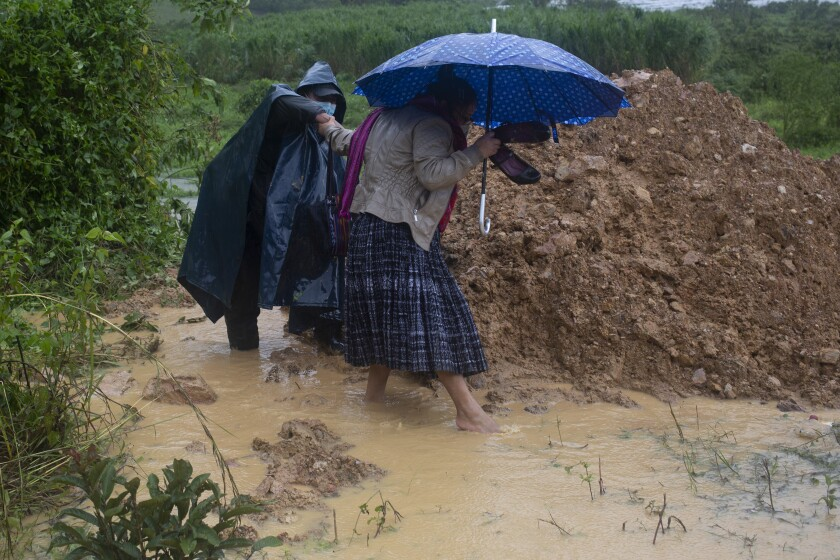 People try to walk around a road blocked by a landslide caused by Hurricane Eta in Purulha, Guatemala, on Friday