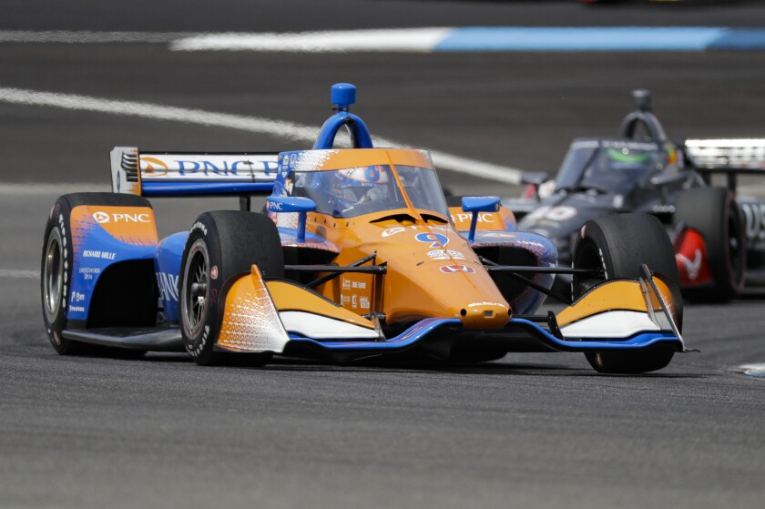 Scott Dixon drives through a turn during the IndyCar Grand Prix race at Indianapolis Motor Speedway on Saturday.