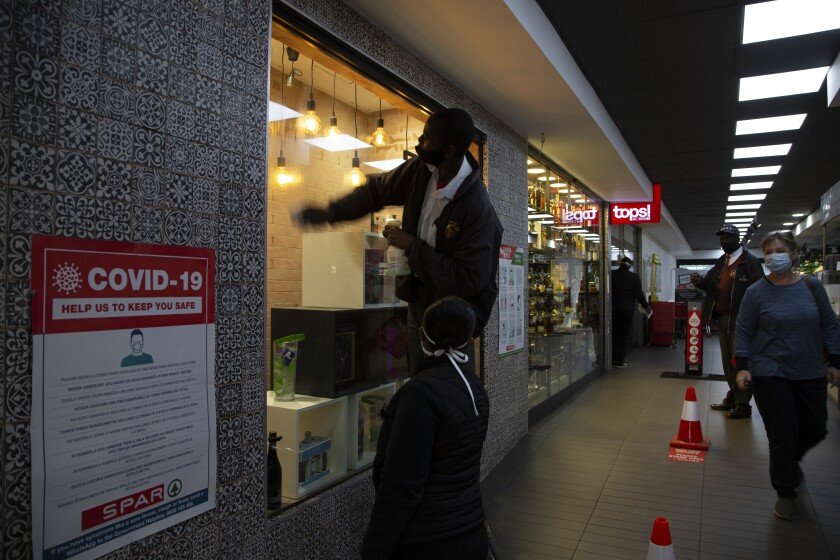A man cleans a store window at a Johannesburg liquor store in Johannesburg Tuesday, Aug. 18, 2020 as the country lifted its coronavirus-linked ban on the sale of alcohol and tobacco products. The purchase of alcohol and cigarettes was banned when the country went into a strict nationwide lockdown on 27 March to stem the spread of coronavirus. (AP Photo/Denis Farrell)